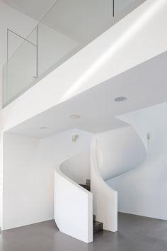 Villa Lumi by Avanto Architects has a curving white concrete staircase
