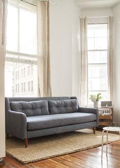 A denim sofa on rich walnut legs