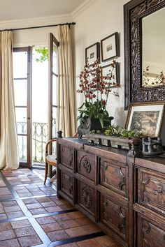 Colonial Traditional Furniture: An antique sideboard on terra-cotta tile floors.