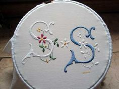 The piece of embroidery is a set of monograms – two S's – for his brother and his fiancee, both of whose names begin with S. It seems that Marika's soon-to-be sister-in-law likes her whitework, while her brother likes her colored embroidery. So Marika cleverly combined the two color options in a double monogram set.