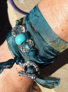 This is so easy to do!      Beaded Ribbon Wrap Boho Style Bracelet      Double length of hand dyed ribbon, clear faceted focal beads and silver tone clasp. 26.5 inches long...just wrap it around your wrist and go!