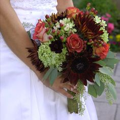 Assorted Fall Wedding Bouquet . Shannon%u2019s bouquet of chocolate sunflowers, green hydrangeas, roses, hypericum berries, chocolate cosmos and eucalyptus leaves by J&J Gardens was a stunning accompaniment to the day%u2019s autumn theme.