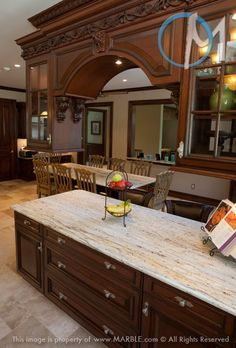 This peninsula overlooks the kitchen table, and both feature New Colonial Dream granite. www.marble.com  This has an Ogee edge. I JUST LOVE, LOVE, LOVE THE ORNATE CABINETS!!!!!!!!