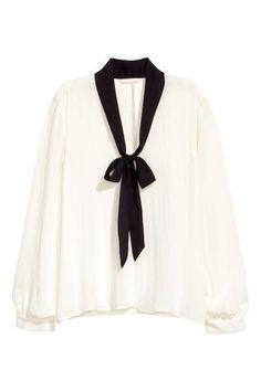 Bluzka z wiązaniem: Szeroka bluzka z cienkiej tkaniny. Dekolt w serek z wiązaniem. Nieco dłuższy tył.