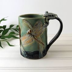 100% handmade botanical pottery coffee mug or tea cup depicting dragonflies, butterflies and a frog in this little spot near the water. The cattails are rising way above you. I drew the picture for this on a secluded lagoon right next to Lake Michigan. No ones around. You hear the insects droning on. Its a peaceful day...  This carved and incised mug is hand built out of high fired porcelain. Glazes are sprayed, then painted on. Much as a painter on a linen canvas. It has a green frog…
