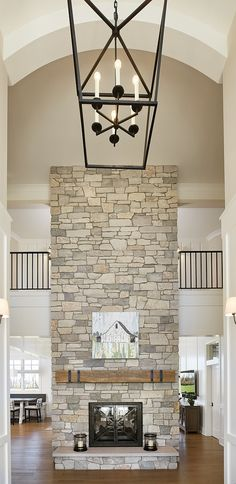 Two story fireplace Stone Fireplace This two-story stone double-sided fireplace is surround with raised natural stone hearth and rustic mantel beams #Twostoryfireplace #StoneFireplace #naturalstonefireplace