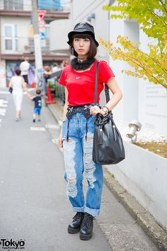 Lana on the street in Harajuku wearing an MYOB bucket hat with a Jouetie t-shirt, ripped jeans with a Bubbles Harajuku garter, boots, and a Goocy tassel bag.