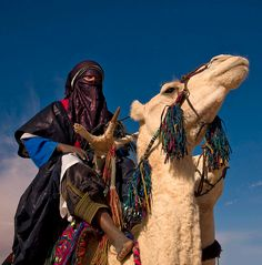 Africa | Tuareg in the desert - Ghadamis Libya Tuareg people are impressive: they wear fantastic clothes with incredible colors. They ride giant camels, and live like in slow mode! Perhaps they've just understood life! Many in Libya come from Niger or Algeria, as for Tuaregs, borders mean nothing.