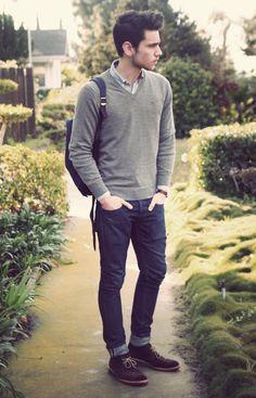 Bota em couro camurça + calça jeans skinny + camisa azul + pulôver em gola 'V' + cinto preto + relório slim com pulseira em couro marrom + mochila azul indigo