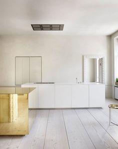 A sculptural brass island adorns this minimal, art-gallery-like kitchen by Swedish design firm Claesson Koivisto Rune.