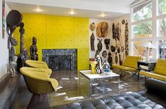 Colorful living room displays a wonderful collection of African statues and artifacts - Decoist