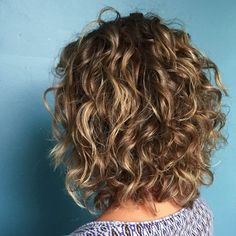 Short haircuts can benefit from dimensional highlights. Aveda stylist Melody added a few highlights to give these short curls extra dimension, then cut and styled with Be Curly.
