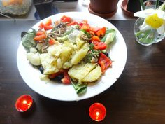 Gloriously good salad with baked potato, spinach, red pepper, olives, horseradish and seeds.