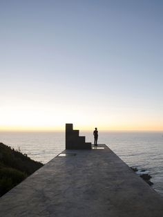 The monolithic structure features predominantly solid concrete elevations, with its elongated proportions lending it the appearance of a wall emerging from the hillside.