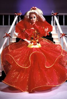 1993 Happy Holiday Barbie  Special Edition  Release Date: 1/1/1993  Product Code: 10824    Wearing a red tulle gown with golden bodice, Barbie® doll is ready to celebrate the season! Her golden bodice is accented by several red sequined and bead poinsettias. There's even a lovely poinsettia in her long flowing hair. What a beautiful vision of holiday cheer!