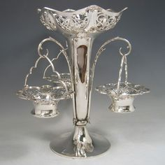 Antique Edwardian sterling silver pierced basket epergne with central vase and three removable pierced baskets. Made by Elkington & Co., of London in 1906.
