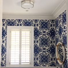 white shutters and blue and white wallpaper.