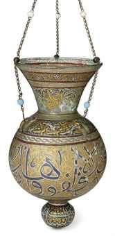 A LARGE GILT AND ENAMELLED CLEAR GLASS MOSQUE LAMP  OTTOMAN SYRIA, 19TH CENTURY  With globular body and flaring neck, the base with rounded knop and pontil mark, with three hanging loops and suspension chains with glass beads, the decoration with alternance of thuluth calligraphy and floral scrolls  15in. (38cm.) high