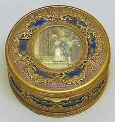 Year: 	1850 - 1925 A French ormolu-mounted porcelain circular box depicting a genre scene painted on ivory, cobalt ground, bow-tied ribbon motif.