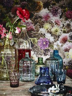 Een verzameling gekleurde vazen en een met bloemen behangen muur passen qua onderwerp mooi bij elkaar.