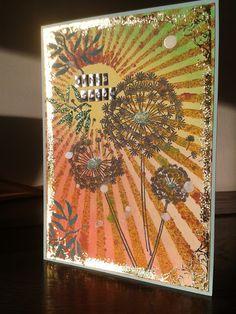 Schablonierter und bestempelter Hintergrund mit gestempelter Pusteblume als Fokus