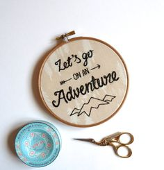 Hand embroidered Lets go on an adventure text with my geometric mountain logo underneath. The design is embroidered using satin stitch with