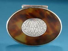 "GEORGE I SILVER & TORTOISESHELL SNUFF BOX -     England, c1720,   The oval box with tortoiseshell lid and base, surrounded by a moulded silver rim and standaway hinge,    the cover inset with a silver oval with cipher monogram MR. 3-1/8"" Wide  x 5/8"" High x 2-5/8"" Deep"
