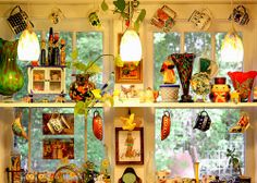 WIndow shelves w colorful cups and pitchers instead of curtains