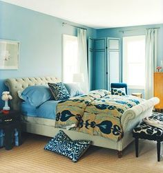 domino bedroom--blue walls, folding upholstered screen, tufted bed, ikat bedding