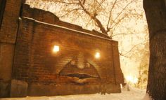 Face with glowing eyes painted on wall by Nikita Nomerz
