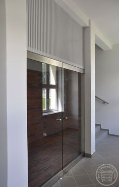 Zabudowa wnęki na klatce schodowej, ścianka całoszklona z blachą perforowaną powyżej wydziela boks ekspozycyjny.