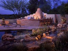 An outdoor kitchen and boulder water feature add coziness and functionality to this outdoor retreat. Water flows in and around the space and gently trickles into the pool. A large L-shaped bar with stone veneer establishes the importance of the outdoor space. Designed for entertainment and enjoyment, this al fresco chiminea