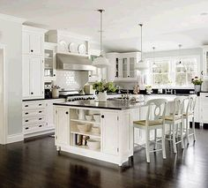 My model kitchen picture - white cabinets, in staggered heights, lots of crown molding, light gray paint, DARK WOOD FLOORS, and the island with open shelving on the side. Almost perfect, I tell you.