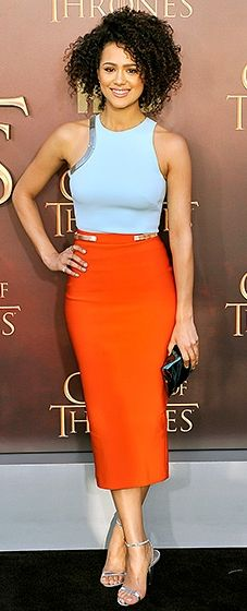 """The GoT beauty teamed a sky blue crop top and a tangerine pencil skirt, both by Mugler. She added Anya Hindmarch's """"Crisp Packet"""" clutch, Stuart Weitzman """"Nudist"""" sandals, and natural curls."""