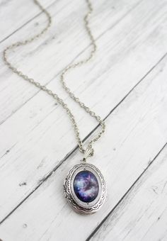 This 18 inch silver chain necklace features a 1 1/4 x 1 inch oval locket that can hold two 1 x 3/4 inch photos. The locket is adorned with a beautiful high quality galaxy print sealed behind a 13 x 18