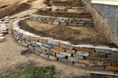 A series of retaining walls under construction hold back the earth of a terraced garden.