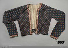 """Kvinnotröja av tryckt bomullstyg, av typen valstryckt 1800-talskattun, blå botten med tryckt """"tyllmönster"""" i svart ."""