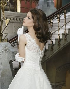 Alencon lace and tulle tea length ball gown features a Sabrina neckline  and silk dupion criss-cross pleated cummberbund. The back of the gown  has a V-back neckline and silk dupion buttons.