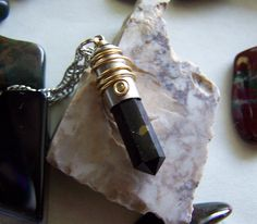 Russian Shungite Wire Wrapped Silver Bullet Jewelry Pendant - Shungite is an ancient composite rock formation that was first discovered in the Karelian region of Russia near a small village called Shunga. The local residents have always had legends and stories about the mysterious restorative powers of the black stone.