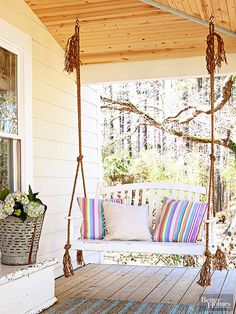 A porch swing found through social media gets a twist of interest hanging from rope instead of chain. The frayed ends at the top keep it casual. A recycled toy trunk provides additional seating and a stoop for flea market garden containers.