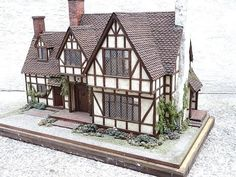A half-timbered English house by Pam Throop built in 1985 and featuring particularly spacious rooms suitable for displaying many miniature furnishings. Another one of Mrs. Estes' houses featured in Miniature Collector Magazine, this house contained many of the Tudor-style furnishings and accessories selling in this auction. Nicely detailed interior and landscaped exterior, and featuring Pam's own handmade light fixtures and character-filled architectural details. Each of the six rooms has…