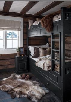 Rustic styled guest bedroom with black bunk beds. Hewn walls and fur pelts. Black Bunk Beds, Bunk Beds With Stairs, Loft Stairs, Cozy Cabin, Cozy House, Cabin Homes, Log Homes, New York Loft, Cozy Bedroom