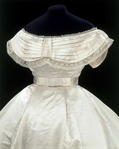"Wedding Dress, Massachusetts, USA: 1867 (made), 3 October 1867 (worn), silk satin, needle lace, cotton and whalebone strips.    ""In the nineteenth century the bride's dress was the focal point of a wedding just as it often is today. The fashionable cut and rich material lavished on this gown show that it was clearly designed for a prosperous bride. With its crisp, simple lines and high waist and gored skirt worn over a crinoline cage, it is similar to styles depicted in contemporary photograp..."