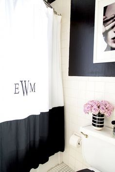 Personalized accessories add feminine flair to this black and white bathroom.
