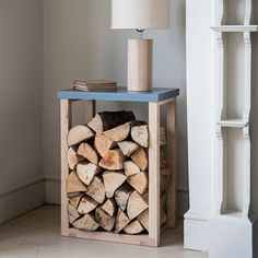 Made of oak with a painted wooden top, this table stores logs neatly and provides valuable table top space for lamps, books, or cups of tea. Where to buy: Clockhouse Log Table, Grace & Glory Indoor Log Storage, Log Store Indoor, Diy Log Store, Log Table, Crate Table, Log Holder, Oak Logs, Firewood Holder, Wood Burner