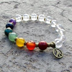 Cool chakra bracelet, made with genuine gemstones, genuine quartz crystal and hand made brass African Trade Beads. Great on men and women alike! You may ask to have the charm removed, just add a note