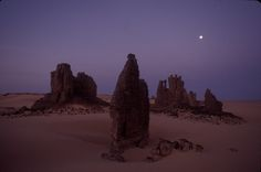 The Sahara Desert at night with the moon in the sky.