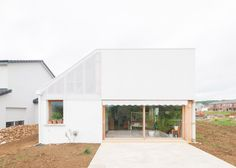 One half of this house in northeast France has a tiled roof and rendered walls, while the other is clad in corrugated plastic and has a chamfered corner