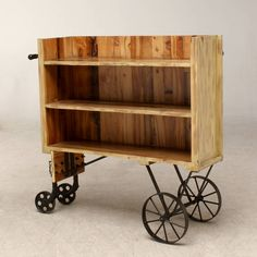 A vintage rustic-looking Factory cart that has three large shelves for storing and displaying a range of products, four wheels and a pull handle for easy manoeuvring.