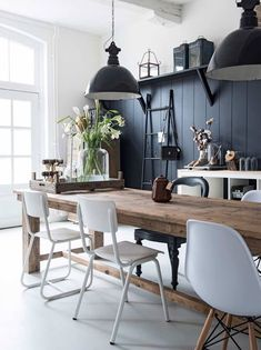 Blue walks, timber flooring, mismatched chairs and hanging lights in dining room.